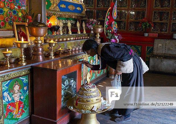 Tibetan woman praying inside a temple of Rongwo monastery  Tongren County  Longwu  China.