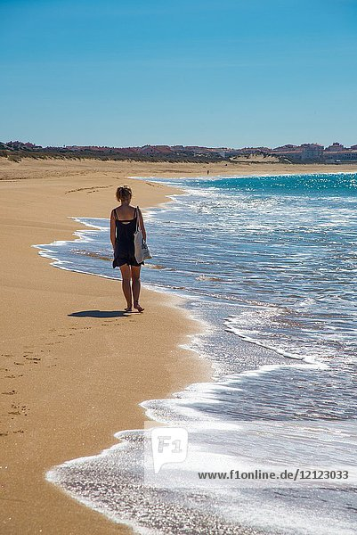 Woman walking at the empty beach in the Bay of Peniche  Portugal