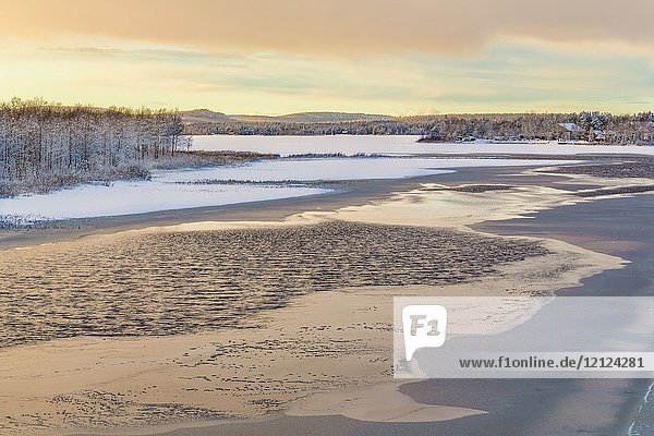 Frozen river in sunset with little open water and sky reflecting making nice colors in the water  mountains in background  Gällivare  Swedish Lapland  Sweden.