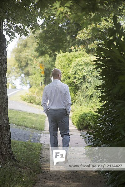 Handsome caucasian man  wearing a pants suit with a white shirt with hands in his pockets  walking son a sidewalk in a small Virginia upper class farm town in the USA in Middleburg.
