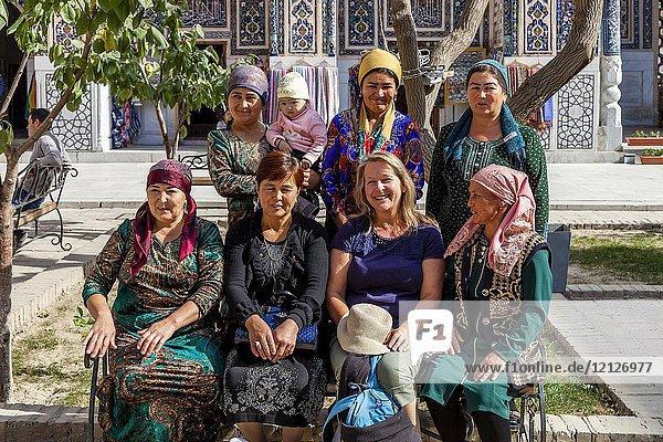 A European Tourist Poses For A Photograph With Local Uzbek Women  The Registan  Samarkand  Uzbekistan.