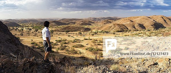 Man looking out at Huab River [Composite Panorama Image] - Huab Under Canvas  Damaraland  Namibia  Africa.