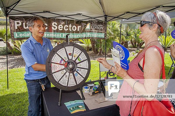 At a utility company Public Sector Local Government Partnership Program booth an Asian American demonstrator spins a 'question wheel' of true-or-false energy-related topics during an environmental street fair in Newport Beach  CA.