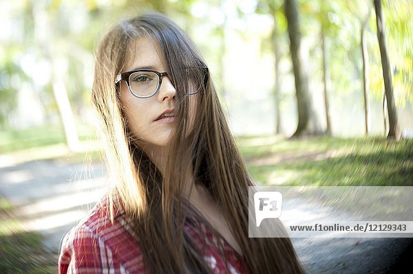 A casual portrait of a 26 year old woman with long brown hair and big glasses  on a country road.