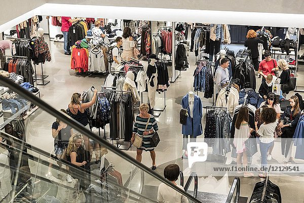 Women's fashion in busy department store.