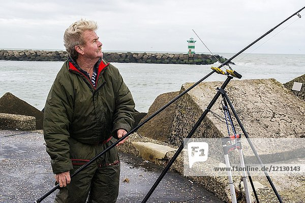 Scheveningen  Netherlands. Retired amature fisherman and his fishing rod on the harbor's north pier. After retirement many men enjoy the outdoors and go fishing at the North Sea shore and coast.