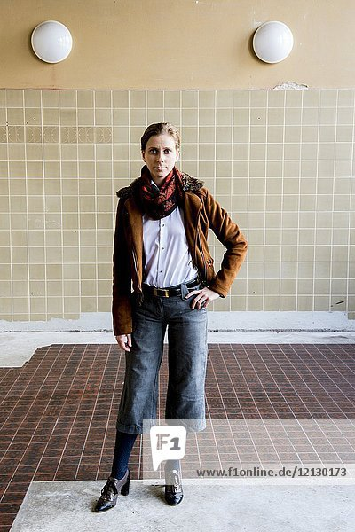 Tilburg  Netherlands. Portrait gender biased woman  wearing men's fashion inside an abandoned industrial environment. Wearing opposite gender's wardrobe defines individual gender identity of an increasing number of people.