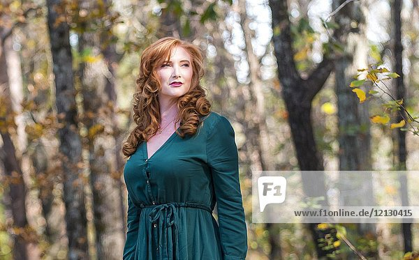 Portrait of a 27 year old redhead woman outdoors in a forest setting.