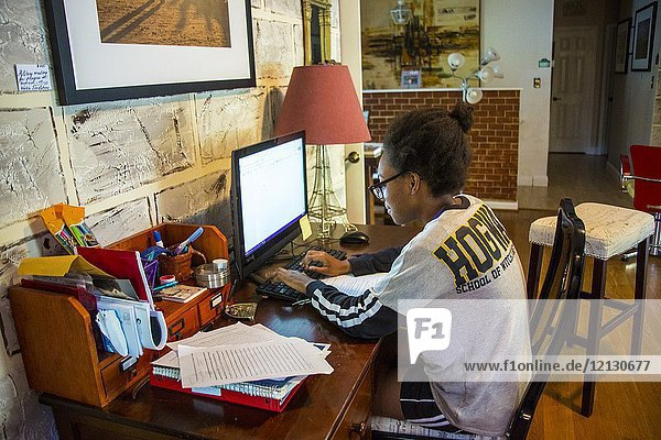 African American teenager,  with glasses,  15 years old,  working on homework at her home in front of the desktop computer.