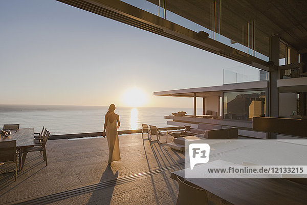 Woman walking on sunset modern  luxury home showcase exterior patio with ocean view