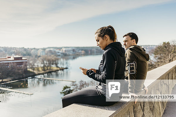 Couple sitting on stone wall in Stockholm  Sweden
