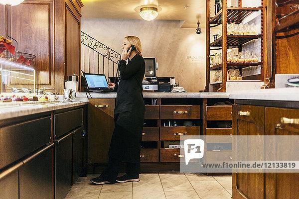 Frau am Telefon an der Bäckerei in Schweden