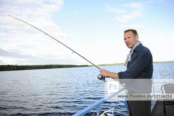 Mann beim Angeln vor dem Pier in Medelpad  Schweden