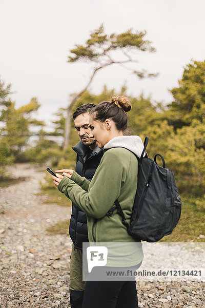 Hiking couple on smart phone in Sodermanland  Sweden