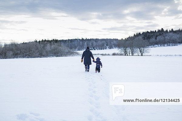 Rückansicht von Mutter und Kind beim Wandern im Schnee