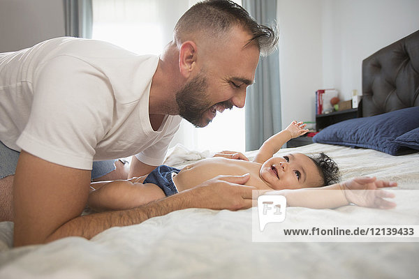 Father laying on bed playing with baby daughter