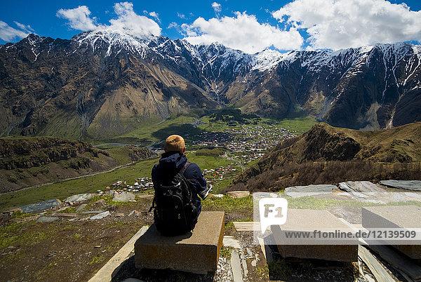 Caucasian man admiring scenic view of village in valley