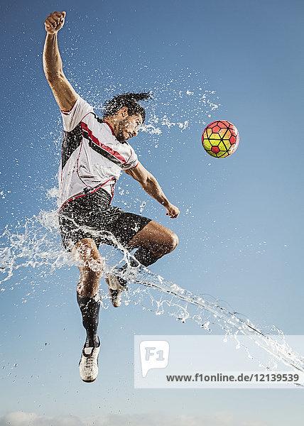 Water spraying on Hispanic man heading soccer ball