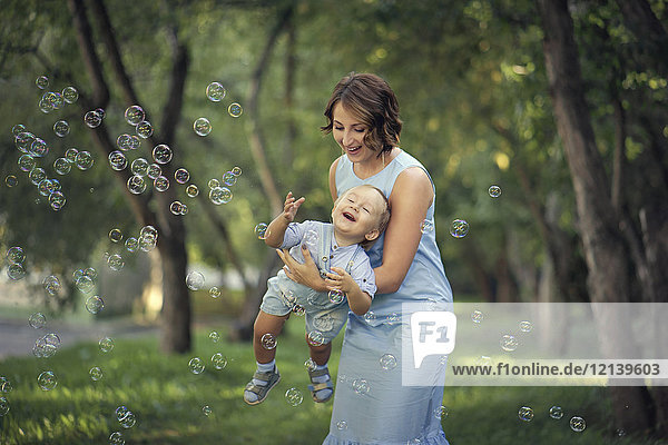 Caucasian mother holding baby son playing with bubbles