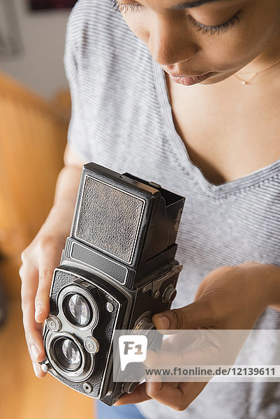 African American woman using old-fashioned camera