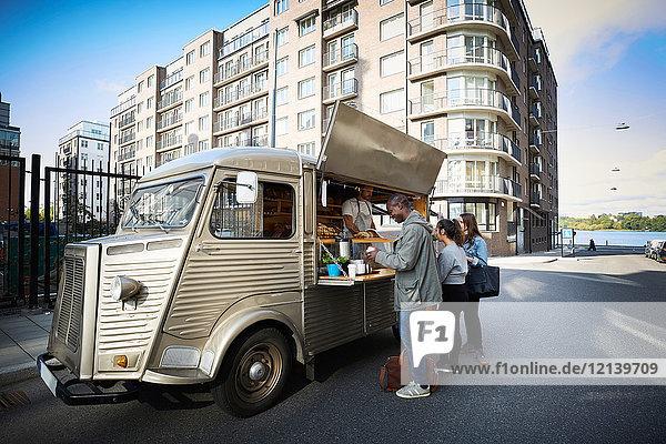 Multiethnische Kunden bestellen bei Food Truck in der Stadt