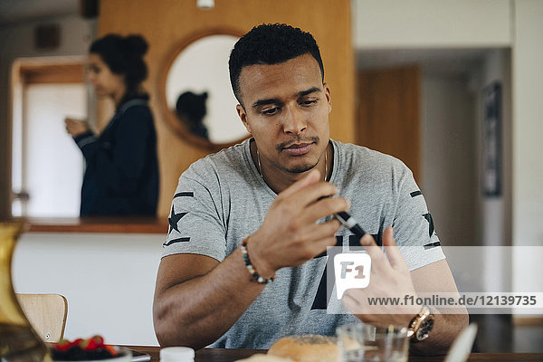 Man checking blood sugar level while having breakfast at home