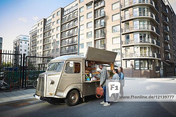 Männliche und weibliche Kunden  die am Food-Truck in der Stadt bestellen.