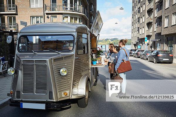 Männliche und weibliche Kunden  die am Lebensmittelwagen stehen  der auf der Stadtstraße parkt.