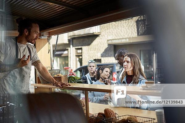 Junger männlicher Besitzer nimmt Auftrag von einer Kundin am Food-Truck in der Stadt entgegen.