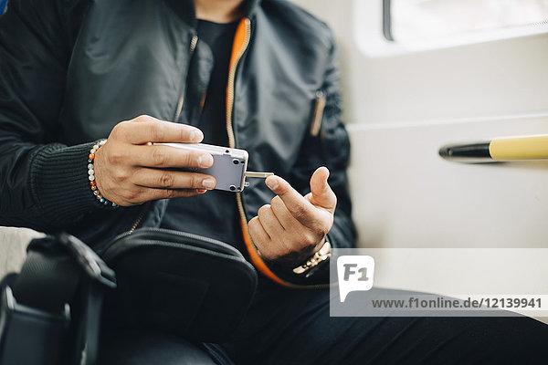 Mann beim Bluttest mit dem Glaukometer im Sitzen im Zug