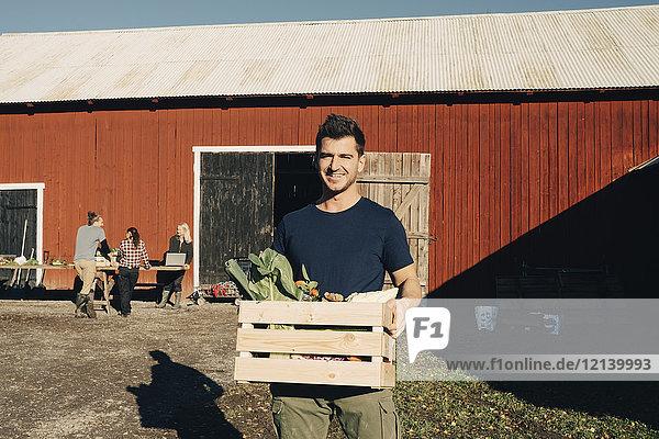 Porträt eines lächelnden erwachsenen Mannes mit Kiste voller Bio-Gemüse mit Scheune im Hintergrund.