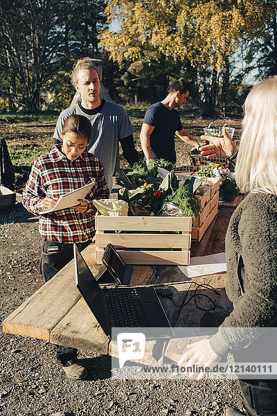 Female farmer selling organic vegetables to customers at market