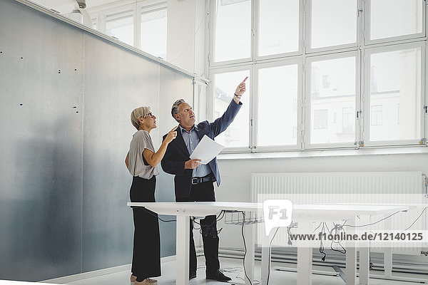 Full length of businessman holding documents while discussing with female colleague in new office