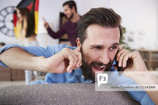 Mann erhält einen Anruf während eines Fußballspiels