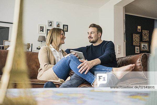Lächelndes Paar sitzt auf der Couch zu Hause mit Tablette