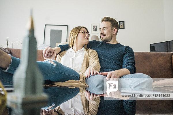 Paar auf der Couch zu Hause sitzend mit Modell des Empire State Building