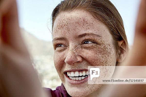 Porträt einer lachenden jungen Frau mit Sommersprossen im Freien