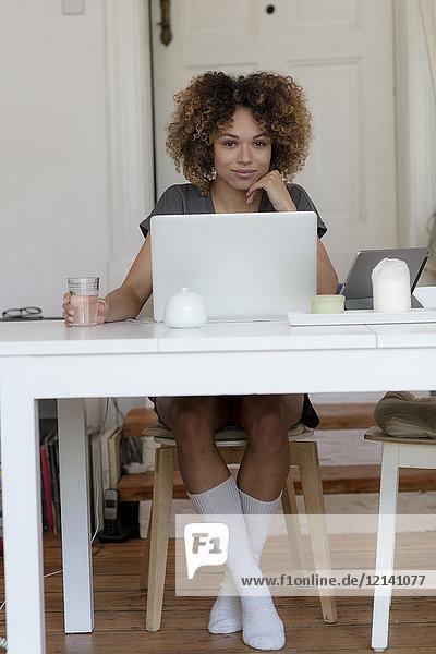 Lächelnde junge Frau sitzt zu Hause am Tisch mit Laptop