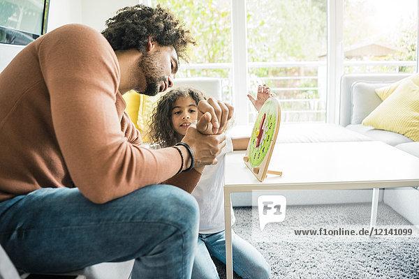 Vater hilft Tochter lernen  die Uhr zu lesen