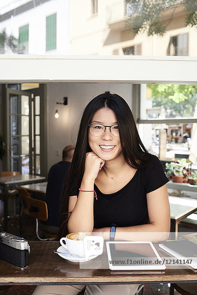 Portrait of an asian young woman smiling at camera in a coffee shop