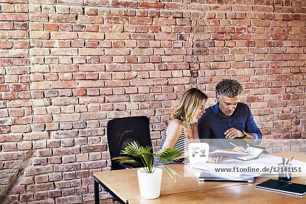 Kollegen mit Plan und Notizbuch arbeiten am Schreibtisch im Büro
