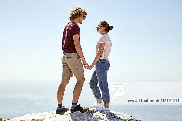 Südafrika  Kapstadt  junges Paar  das auf einem Berg an der Küste steht und Händchen hält.