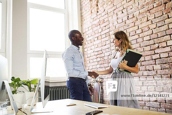 Zwei Kollegen beim Händeschütteln im Büro