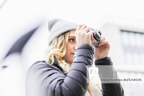 Junge Frau beim Fotografieren mit Vintage-Kamera
