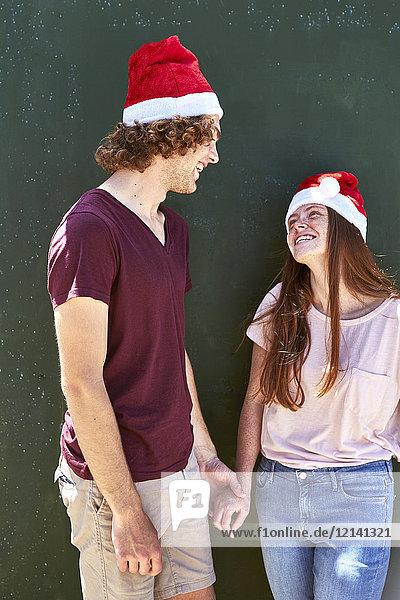 Junges Paar mit Weihnachtsmützen lächelt sich an.