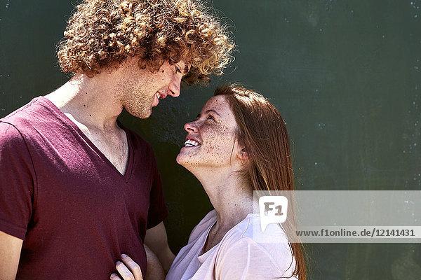 Lächelndes junges verliebtes Paar schaut sich an