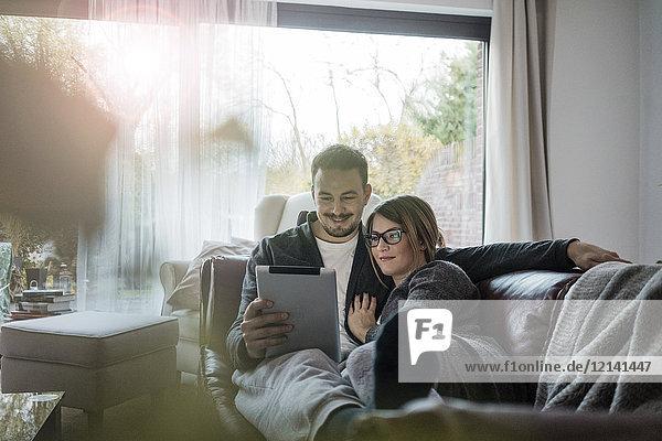 Lächelndes Paar liegt auf der Couch zu Hause und teilt sich das Tablett.