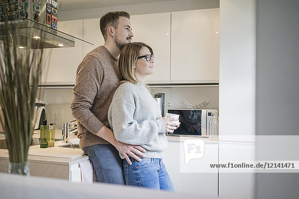 Affectionate couple standing in kitchen at home