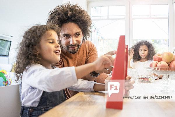 Vater sitzt mit seiner Tochter am Tisch und lernt mit einem Rechenschieber zu kakulieren.