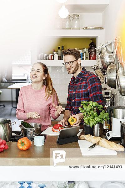 Glückliches junges Paar mit Tablettenkochen in der Küche